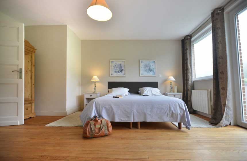 The spacious master bedroom at Villa des Groseilliers self-catering gite comes complete with a balcony…